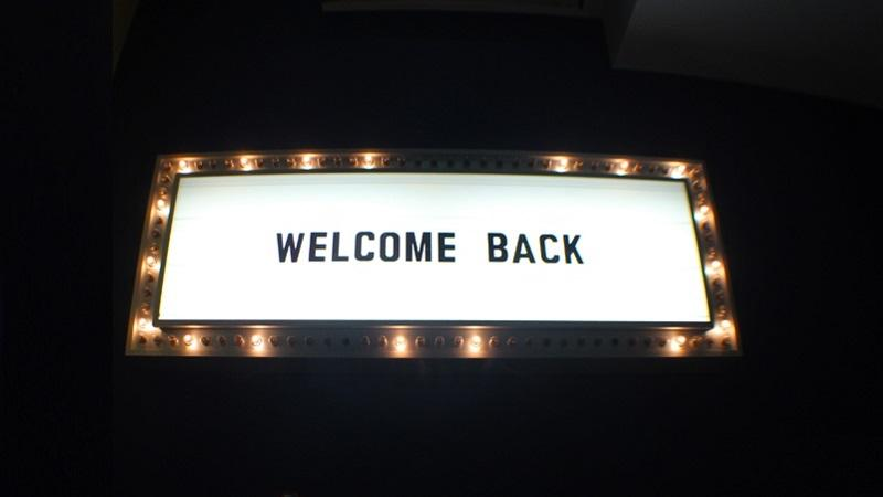 An image of a lighted sign that proclaims 'Welcome back'