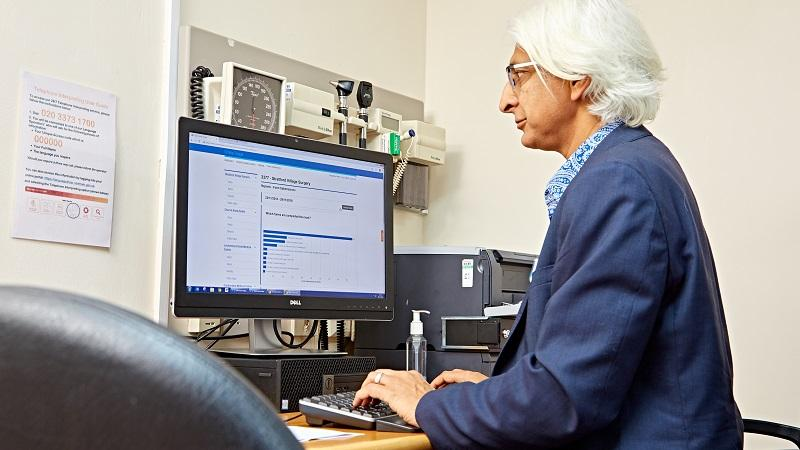 An image of  Dr Bhupinder Kohli of Stratford Village Surgery, working on the computer at his desk