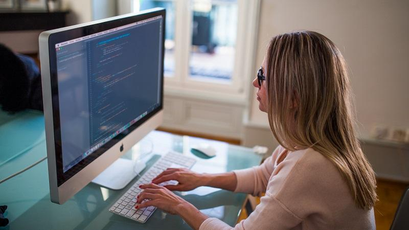 An image of a woman sitting at a Mac and coding