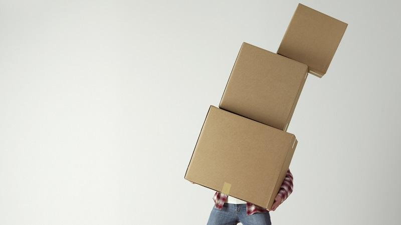 A close up image of a man - whose face we cannot see - struggling to carry several boxes stacked on top of one another
