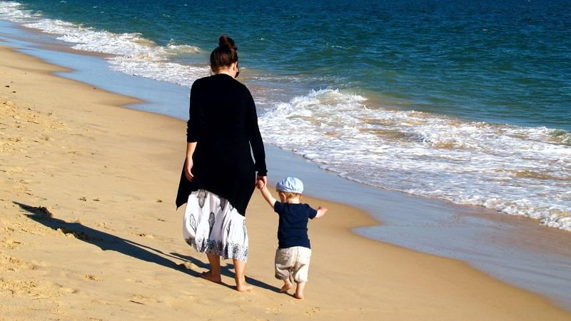 An image of a mother and a son walking on a beach