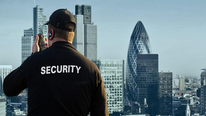 An image of a security guard speaking into a walkie-talkie set against a backdrop of buildings in the City of London