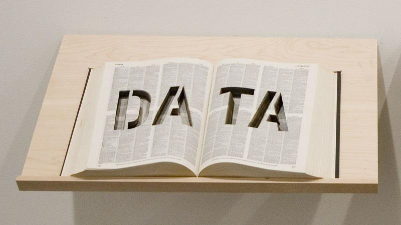 An image of an open book on a plinth with the outline of the word 'DATA' cut out of the pages