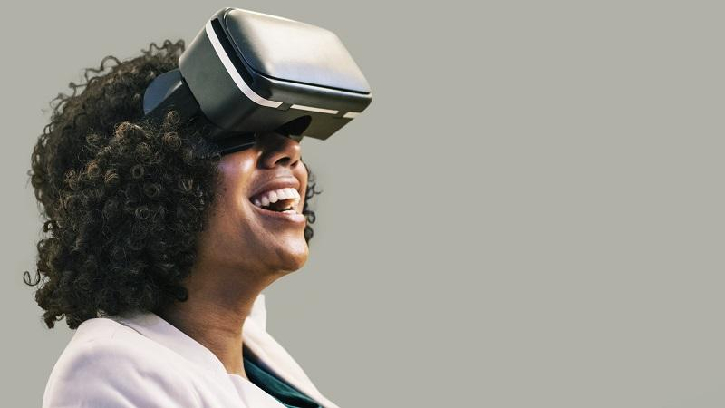 An image of a smiling woman wearing a virtual reality headset