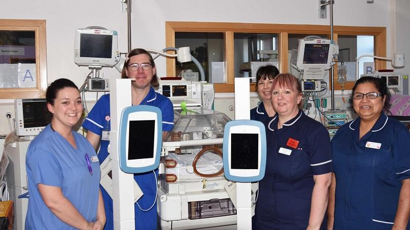 An image of neonatal department staff with two cart-mounted iPads