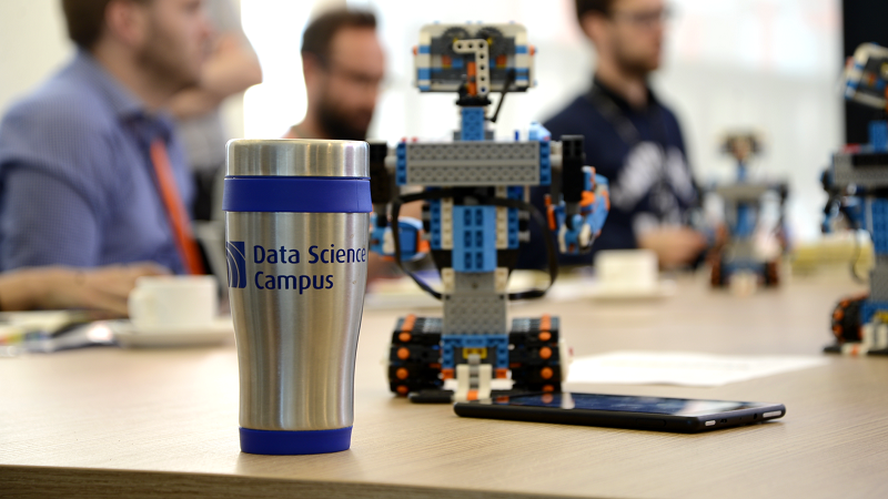 An image of workers at the ONS Data Science Campus, with a branded cup and a robot in the foreground