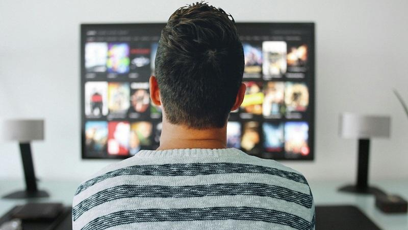 An image of the back of a man's head with the menu of an online streaming service on a large TV screen