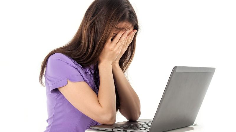 An image of a woman in front of a laptop with her face in hands