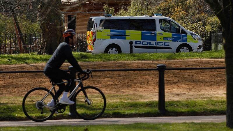 Hyde Park cyclist with police van in background