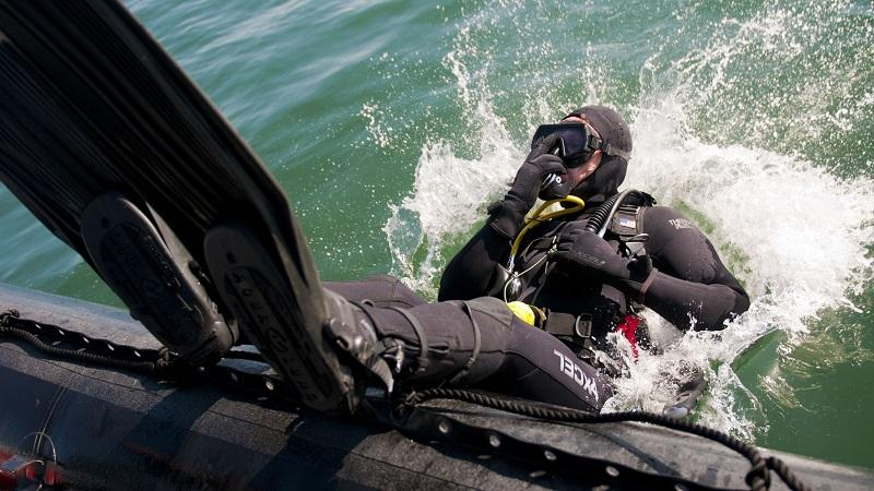 An image of a military diver diving backwards into the sea