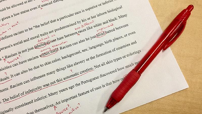 An image of a red pen on top of a heavily corrected piece of essay work