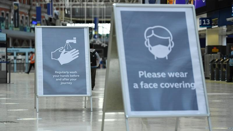 An image of signs at Waterloo station in London asking people to wear face masks and wash their hands