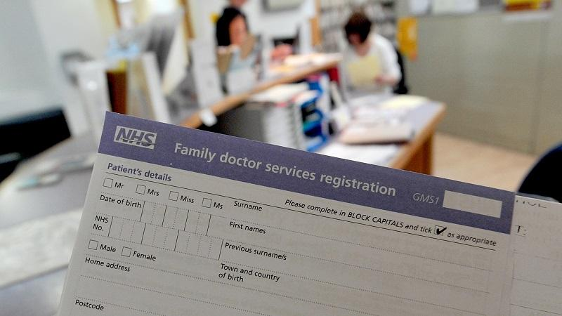 Close up image of a patient registration form with a doctors surgery in the background