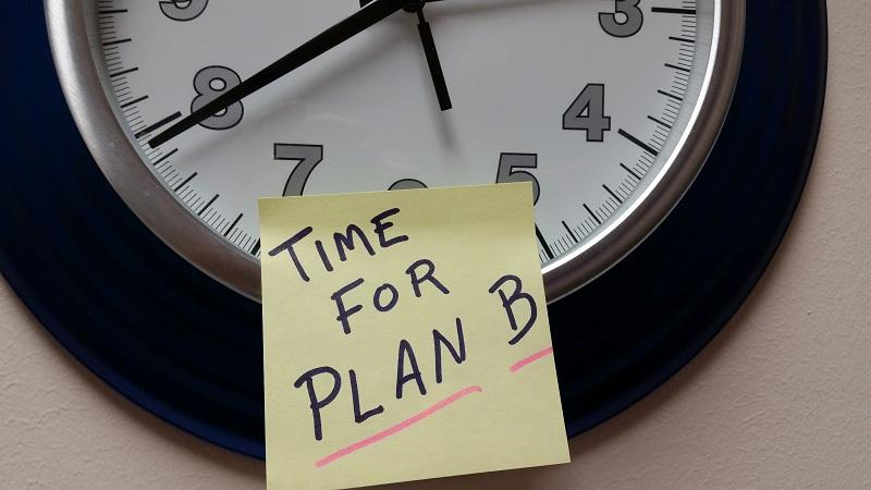 An image of a clock, to which is stuck a sticky note reading 'time for Plan B'