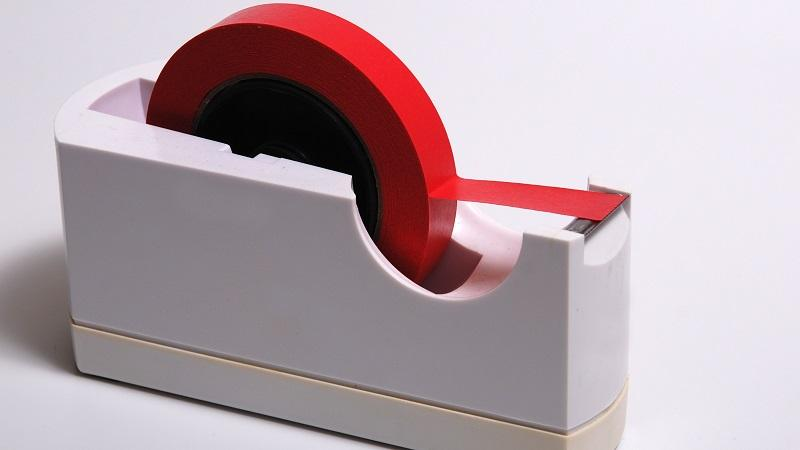 An image of a sellotape dispenser with red tape