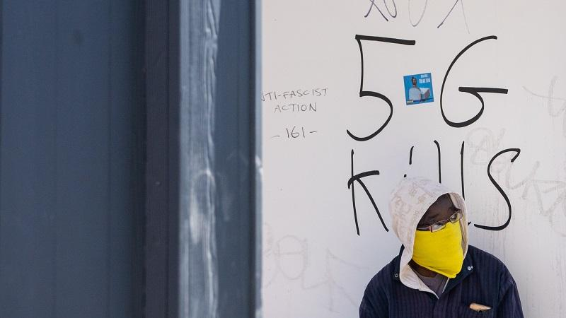 An image of a young man standing in front of a wall where someone has graffitied '5G Kills'