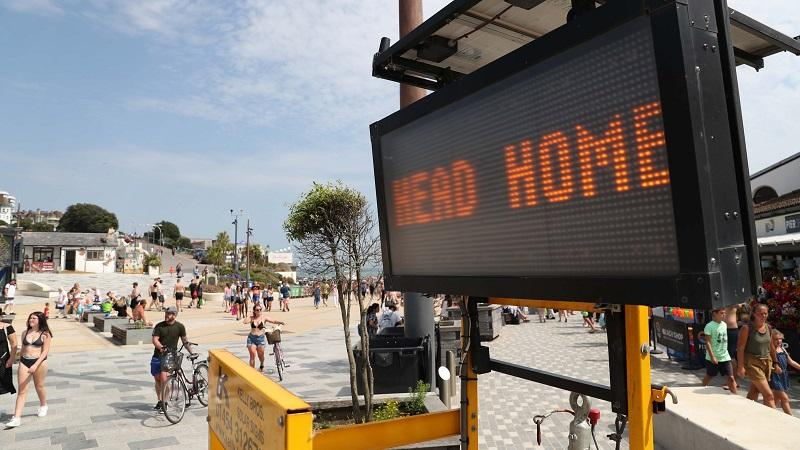 An image of a sign asking visitors to Bournemouth beach to 'Head home'