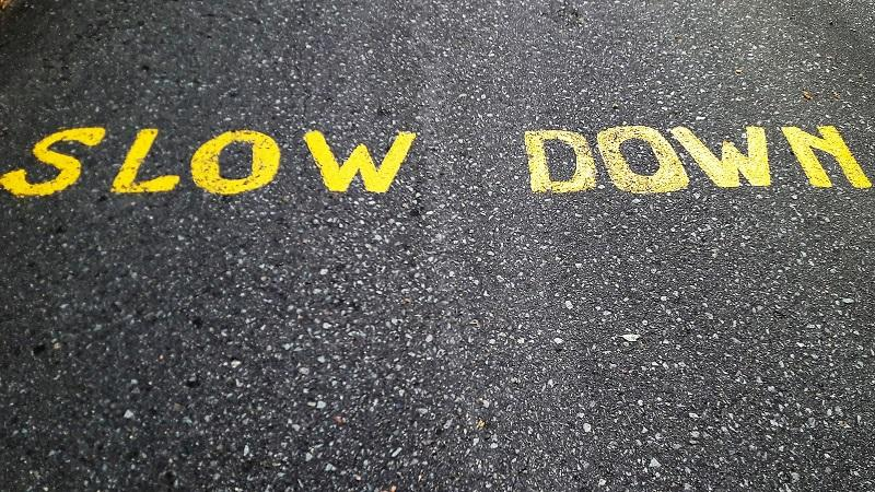 An image of the words 'Slow down' painted on a road