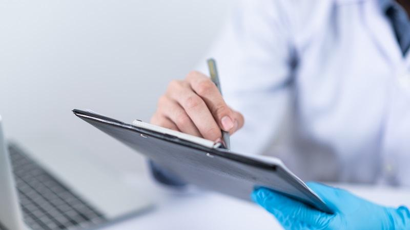 Close-up image of a doctor's hand making notes on a clipboard with a computer in the background