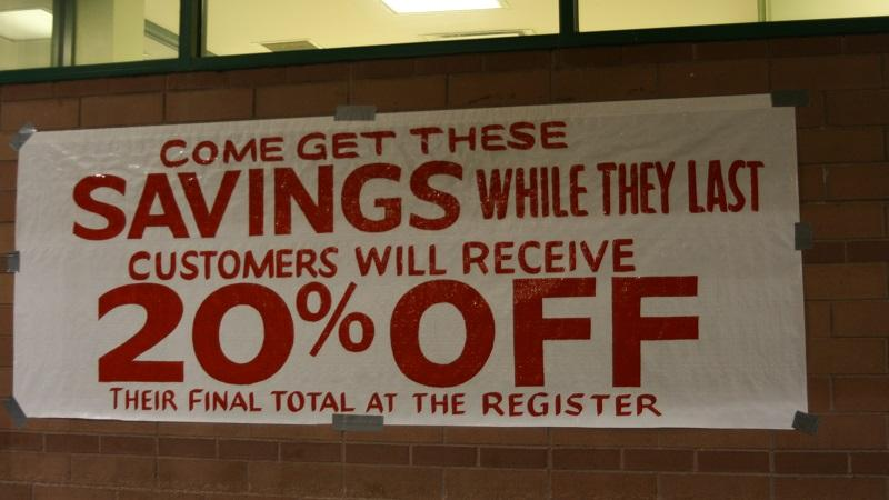 A sign posted on the outside of a store, promising customers 20% savings