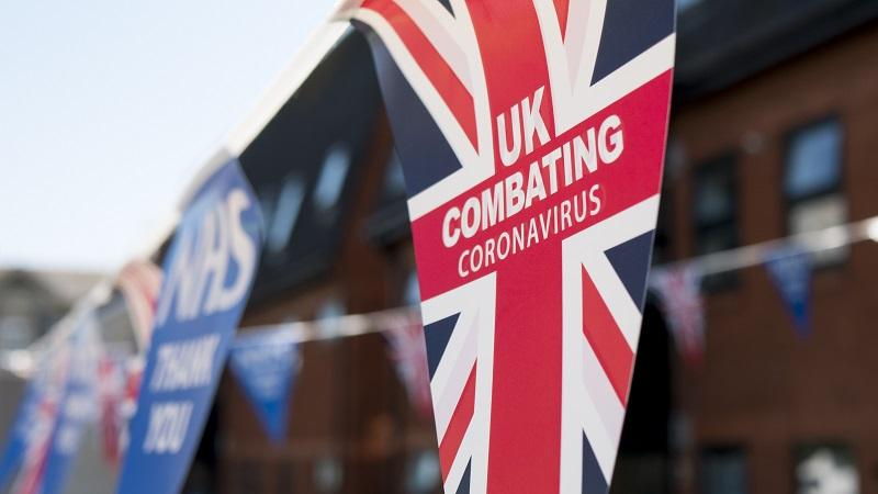An image of bunting flags with a Union flag reading 'UK combating coronavirus' in the foreground