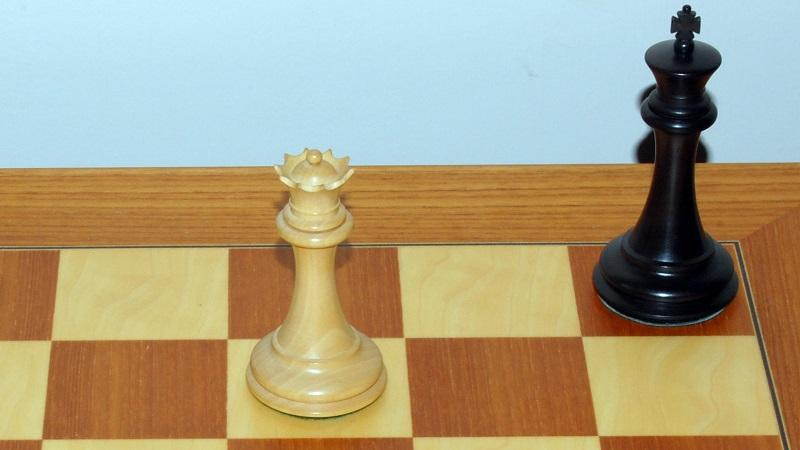 An image of a king and a queen on a chessboard in a stalemate scenario