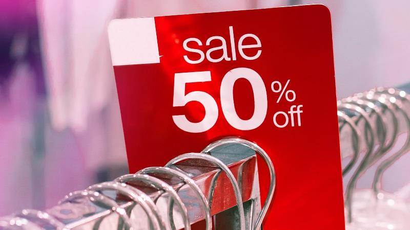 An image of a sign on a rack of garments reading 'Sale 50% off'