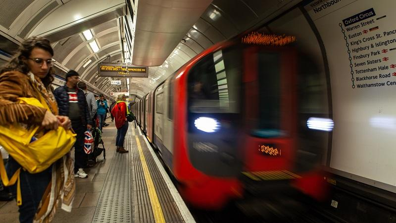 An image of passengers preparing to board a London Underground train arriving into Oxford Circus station