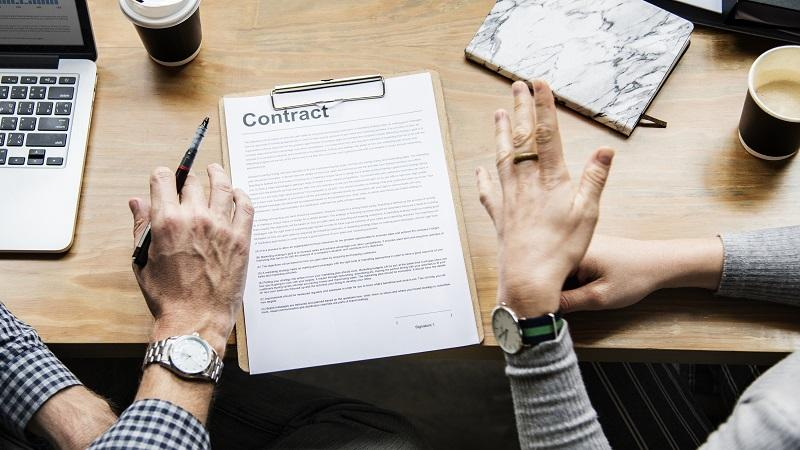 An image of a contract being discussed by two people whose faces remain out of shot