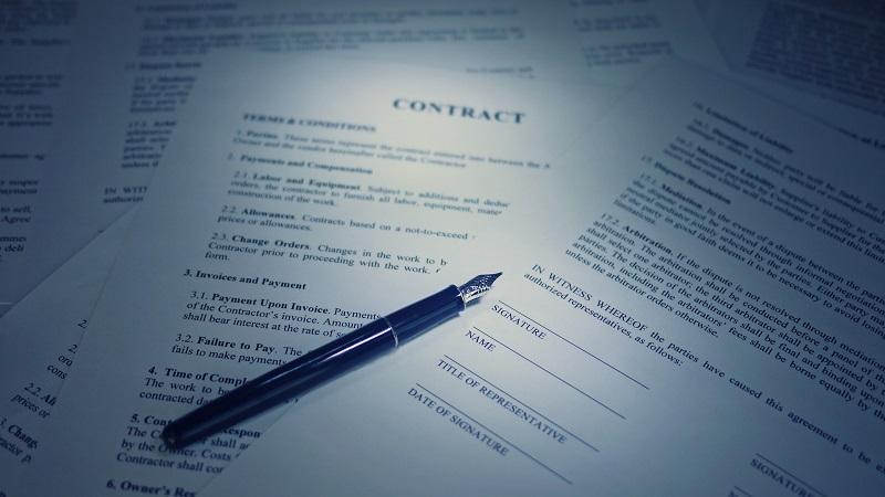 An image of a pile of paper contract documents