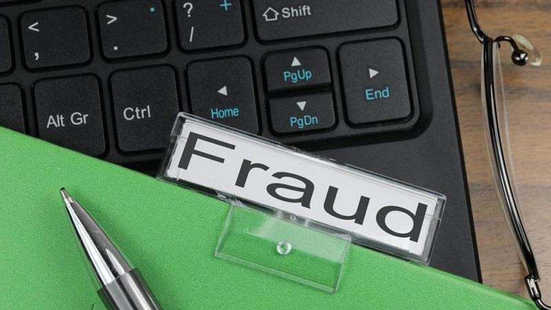 An image of a pen and a clipboard - with a header reading 'fraud' - lying on top of a computer keyboard