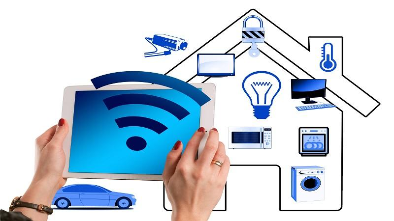 An illustration including multiple devices being controlled from a tablet, with the outline of a house in the background