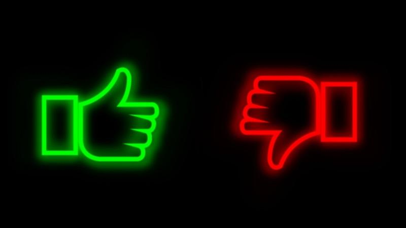 An illustration of neon green thumbs up and red thumbs down symbols on a black background