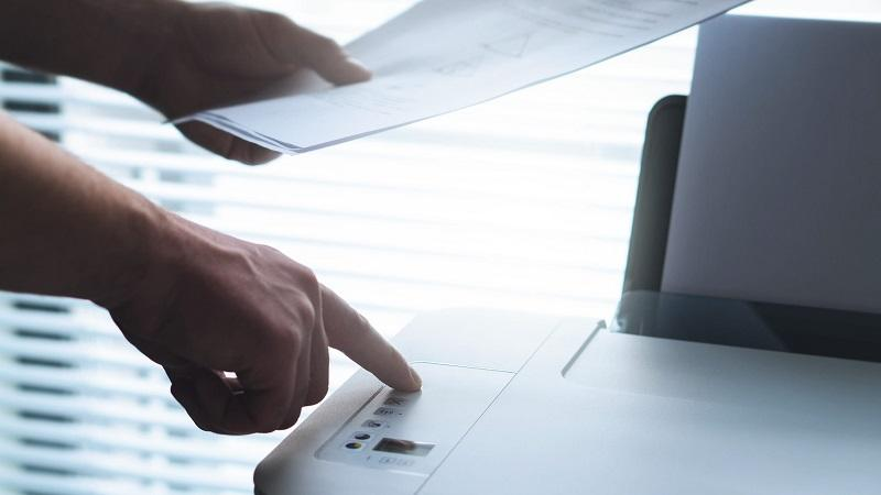 A close-up image of a person pressing a button on a printer, while holding freshly printed sheets of paper in their other hand