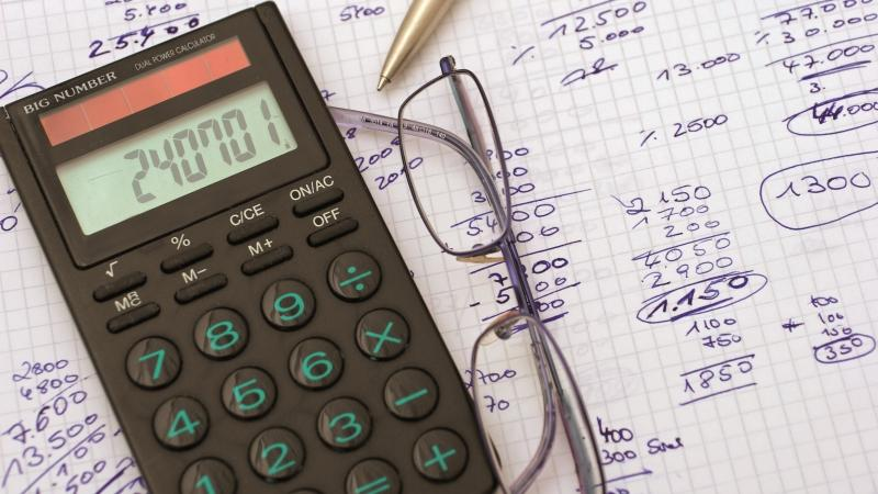 Calculator, glasses and financial sums on a notebook