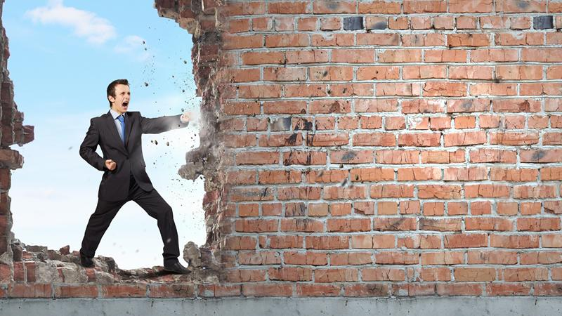 A man forcing his way through a wall