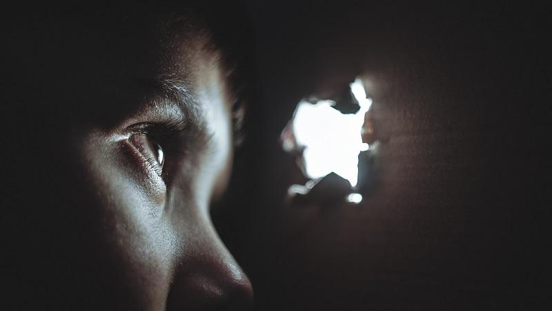 An image of a young man spying through a peephole