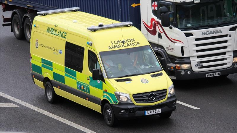 An image of a London Ambulance, in the foreground, driving on the M25 motorway next to a large lorry