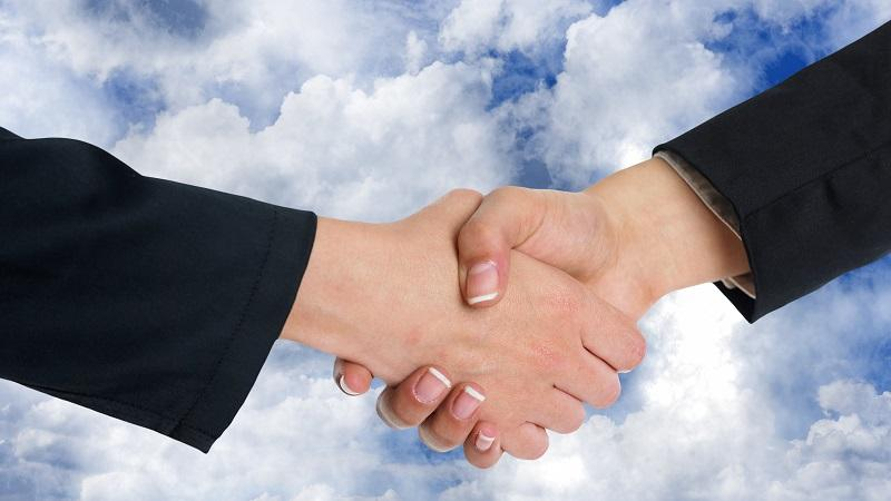 An image of a handshake taking place in front of a blue sky with white clouds