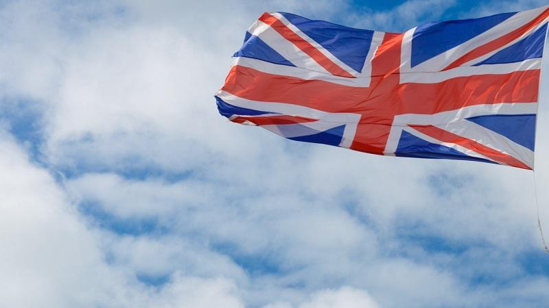 An image of a union flag flying against the background of clouds