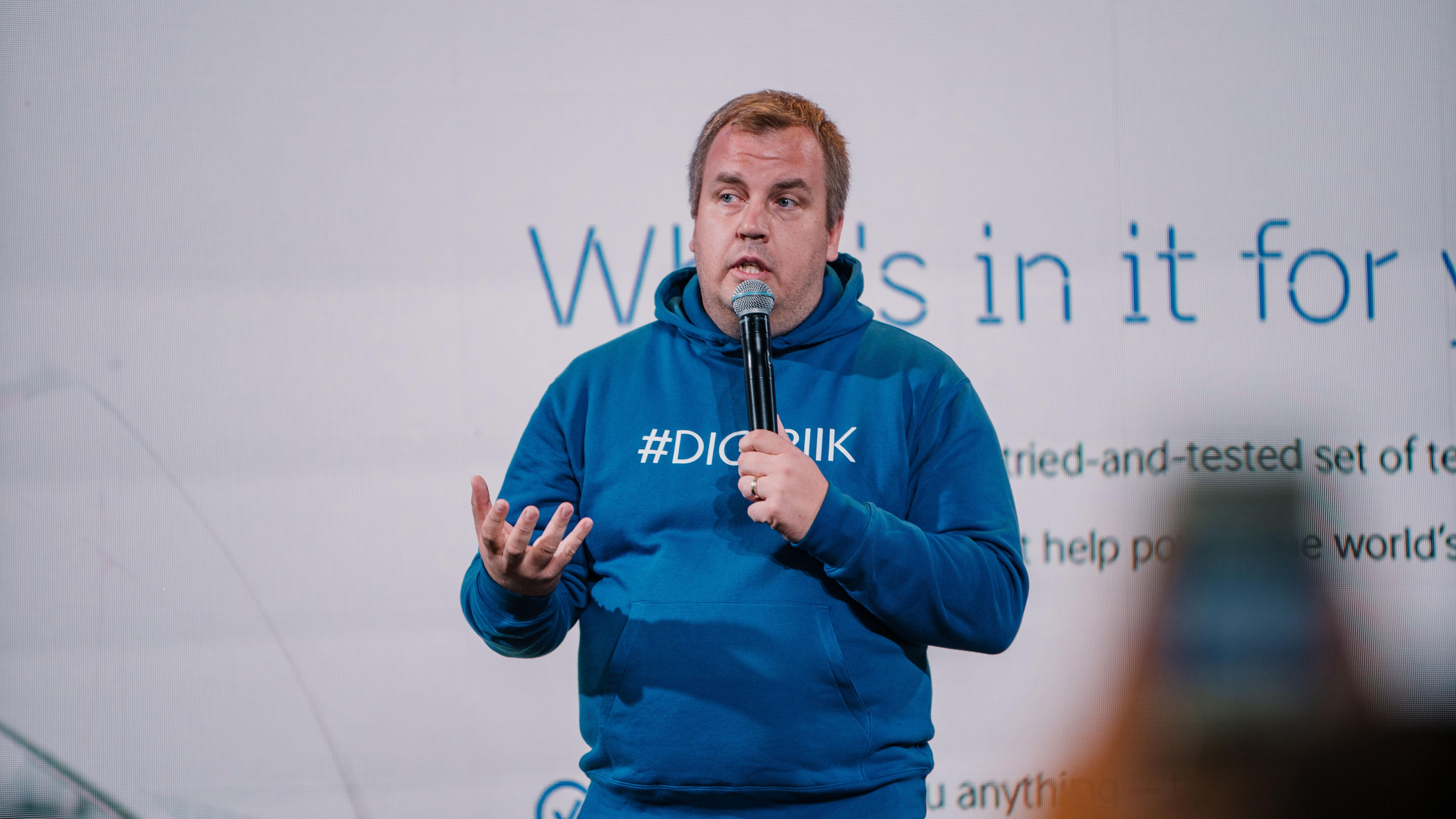 A picture showing Siim Sikkut giving a presentation in a bright blue hooded sweatshirt